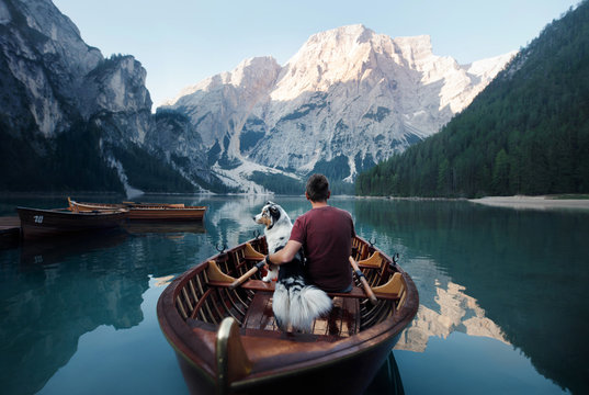 man and dog in a boat on a mountain lake. Trip with a pet to Italy. Australian Shepherd Dog and its owner