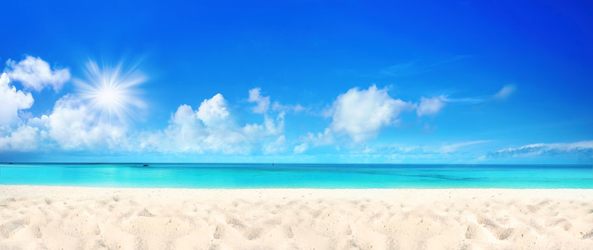 Beautiful beach with white sand, turquoise ocean water and blue sky with clouds in sunny day. Panoramic view. Natural background for summer vacation.