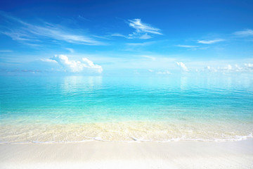 Beautiful sandy beach with white sand and rolling calm wave of turquoise ocean on Sunny day. White clouds in blue sky are reflected in water.  Maldives, perfect scenery landscape, copy space.