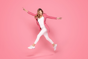 Crazy girl jumping in studio. Wall mural
