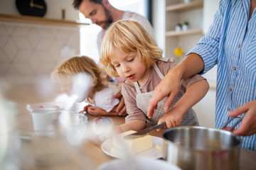 Young family with two small children indoors in kitchen, preparing food.