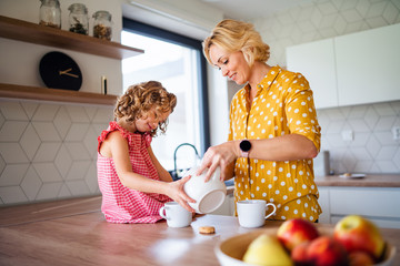 Wall Mural - A cute small girl with mother indoors in kitchen at home.