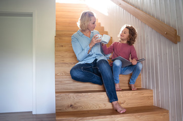 Wall Mural - A cute small girl with mother indoors at home, sitting on staircase.