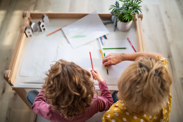 A top view of small girl with mother indoors at home, drawing pictures.