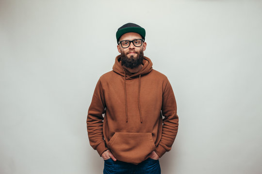 Handsome hipster guy with beard wearing brown blank hoodie or hoody and black cap with space for your logo or design on white background. Mockup for print