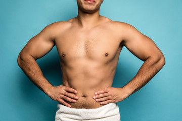 Beauty portrait of half naked handsome young man with beautiful torso dressed in towel touching isolated over blue background