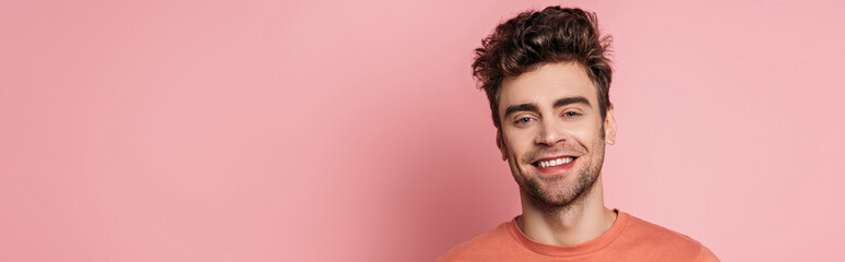 panoramic shot of happy young man smiling at camera on pink background Fotobehang