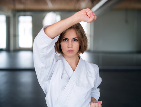 A young woman practising karate indoors in gym.