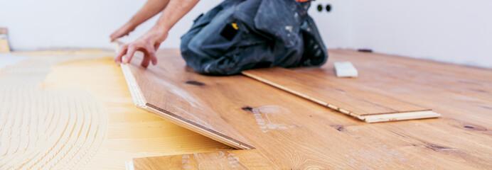 Handwerker verleget Parkett boden in einem modernen neubau Haus