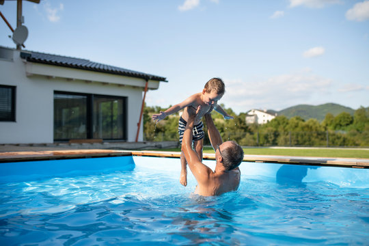A father with small son playing in swimming pool outdoors.