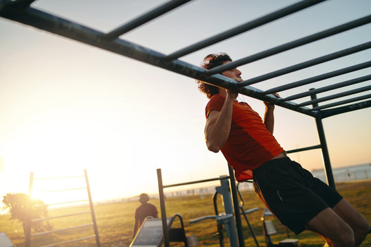 Fit young man doing pull-ups at an outdoor gym park during bright hot summers day