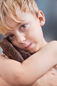 Portrait of Caucasian boy wiping his face with towel