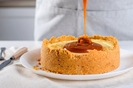 Close up of confectioner decorating orange cheesecake with caramel