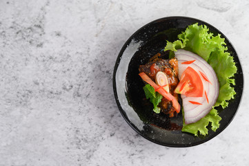 Appetizing Spicy Canned Sardine salad in spicy sauce in black ceramic bowl