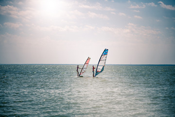 Romance in the sea couple man and woman together sailing on a windsurfing board while on vacation in south