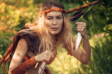 Beautiful girl archer with long blond hair with bow and arrowson a back holding two steel knifes cold arms