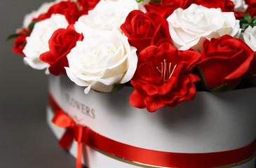 Flowers in bloom: Bouquet of red and white roses on a gray background.