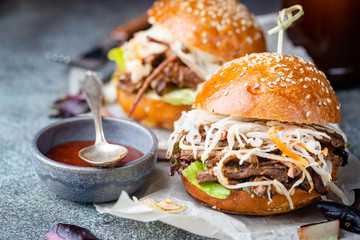 Pulled beef burger with cabbage salad and bbq sauce on paper