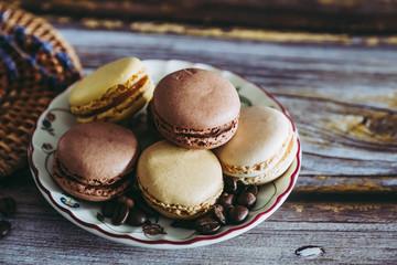Macarons praline vanille café chocolat sur une coupelle en céramique