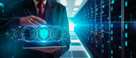 Cyber Security Data Protection, precaution and security in business big data technology,Technology, Internet and network concept.businessman holding tablet and icon shield guard on server background. Papier Peint