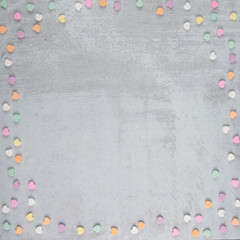 square shaped scattered conversation heart pastel colored candies for Valentine's Day on Gray Grey Cement background and copy space for text and writing