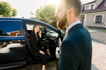 Young beautiful business woman getting out the front door in her car. Driver or business partner helping woman to get outside the car