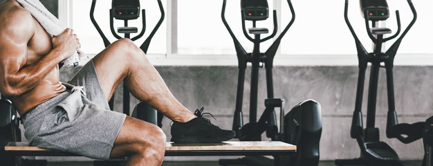 Foto op Aluminium Fitness Fitness man with dumbbell tired and resting in gym