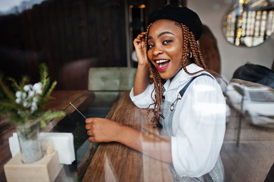 African american woman in overalls and beret sitting on cafe against glass window.