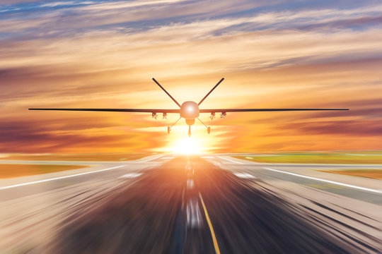 Military unmanned aerial vehicle takes off from runway at a military base in the evening at sunset.