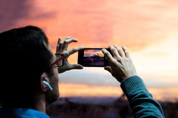 Man with glasses and headphones making a photo at sunset at the airport with his cellphone