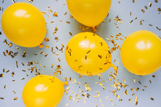 balloons and confetti on blue table top view. Festive or party background. Flat lay style. Copy space for text.