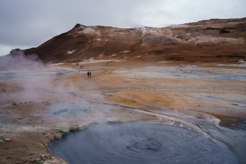 Isolated people walking past smoking fumaroles and boiling mud pots before the mountain range -- Geothermal Park, Namafjall, Iceland