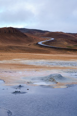 Isolated 4WD car driving down a snaking road across the boiling mud pots Geothermal Park, Namafjall, Iceland