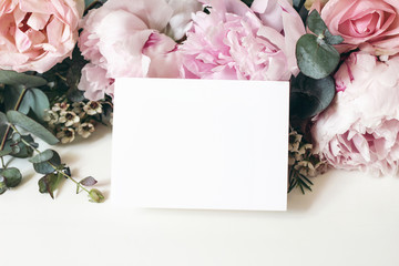 Wedding, birthday stationery mock-up scene. Blank greeting card, invitation. Decorative floral composition. Closeup of pink roses petals, peonies, hydrangea flowers, eucalyptus on white table.