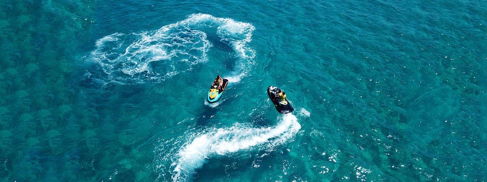 Aerial drone ultra wide photo of jet ski watercraft couple cruising in high speed in tropical exotic bay with turquoise sea