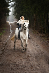 A little village girl in modest clothes walks in the winter with her little white pony in the...