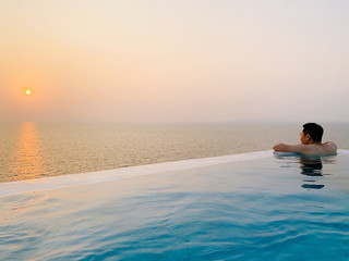 Young man soaking and swimming in an infinity pool with beautiful and peaceful ocean and sunset view during his holiday. Solo travel for weekend getaway and lifestyle concept
