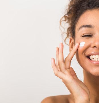 Face care. Happy black woman applying moisturizer cream on cheek