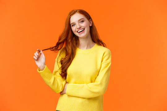 Carefree good-looking, smiling toothy redhead woman, girl with ginger hair laughing as chatting friends, rolling curl on hair, tilt head and smiling joyfully, having conversation, orange background