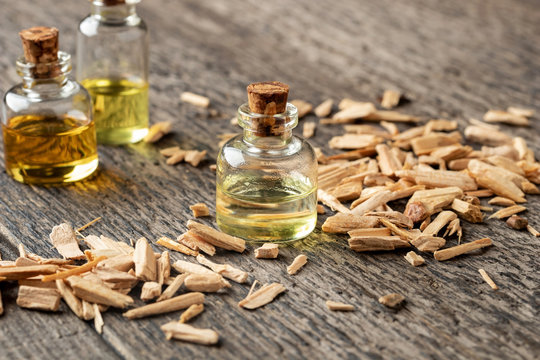 Bottles of essential oil with cedar wood chips