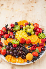 Wall Mural - Healthy fruit platter, strawberries raspberries oranges plums apples kiwis grapes blueberries mango persimmon on wooden table, copy space for text, selective focus