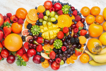 Wall Mural - Healthy platter with colorful rainbow fruits, strawberries raspberries oranges plums apples kiwis grapes blueberries mango persimmon, top view, copy space