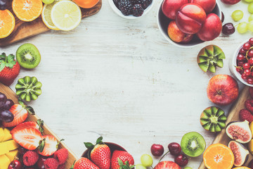 Wall Mural - Healthy raw breakfast background, cut fruits, strawberries raspberries oranges plums apples kiwis grapes blueberries mango persimmon, on white table, copy space, top view, selective focus