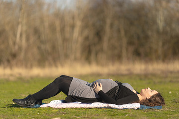 Pregnant woman resting on her back on the lawn