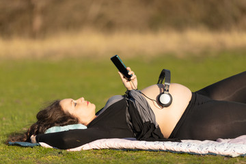 Pregnant woman with headphones over her belly