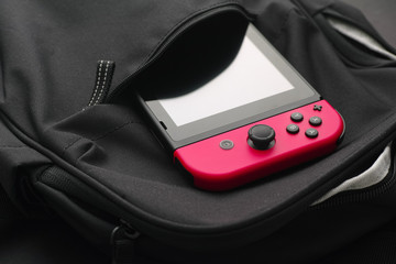 Tambov, Russian Federation - January 19, 2020 Nintendo Switch video game console sticking out of a black backpack.