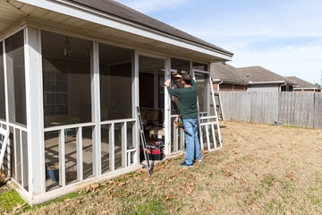 Homeowner works on repairing door to screened in back porch