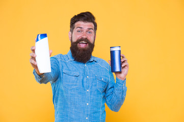 Good choice. Happy hipster hold shampoo and conditioner yellow background. Brutal hipster with hair care products. Bearded hipster with cleansing cosmetics. Grooming routine for hipster