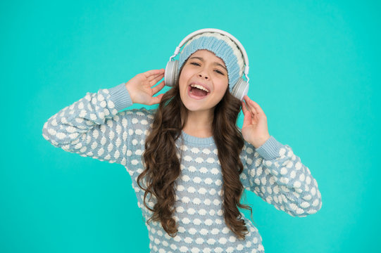cheerful small child knitted sweater and earphones. singing kid turquoise background. her favorite winter songs. happy girl enjoy winter playlist. music mood. song to motivate you in cold weather