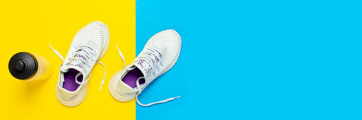 White running shoes and a water bottle on an abstract yellow and blue background. Concept of running, training, sport. Banner. Flat lay, top view